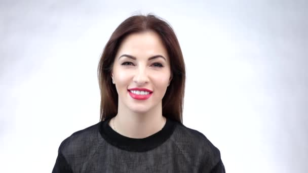 Young girl playful winking brunette woman with brown hairstyle showing trendy makeup. Slow motion