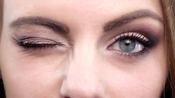 Frau zwinkert. Blaue Augen. Nahaufnahme