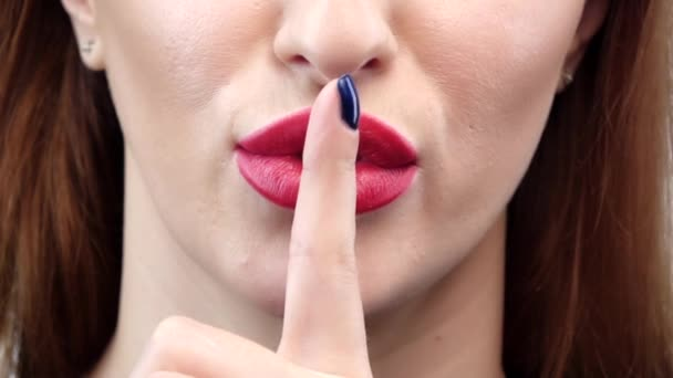 Woman holding her finger to her lips in a gesture for silence. Close up. Slow motion
