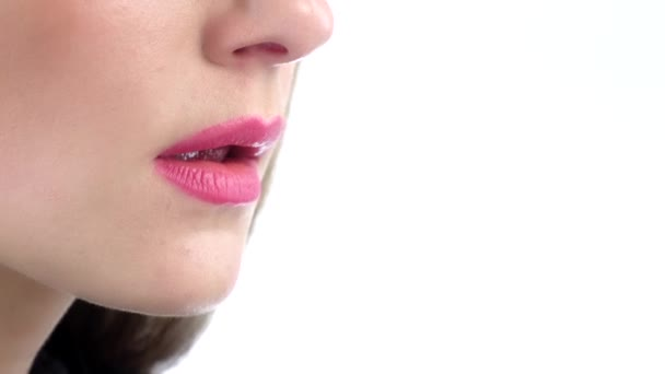 Woman licking a pink shiny lollipop. White. Close up. Slow motion