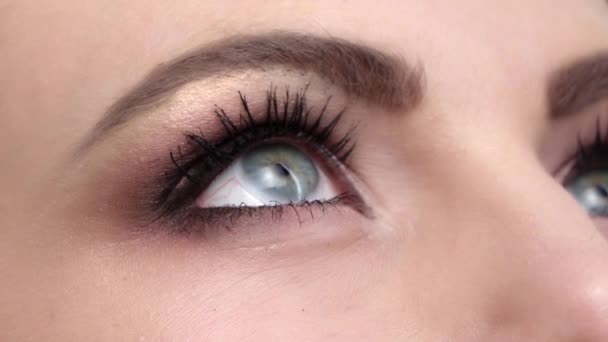 Woman with beautiful blue eyes and long black eyelashes and bright make, contact lenses, close up, slow motion