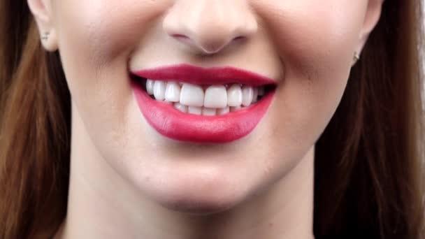 schöne lächelnde junge Frau mit perfekter Haut, rotem Lippenstift und Zähnen. Nahaufnahme. Zeitlupe