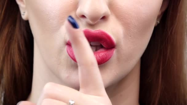 Woman holding her finger to her lips in a gesture for silence. Closeup