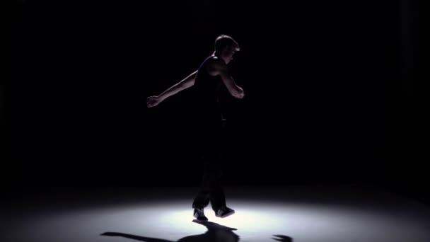 Young blonde dancer man dancing breakdance on black, slow motion