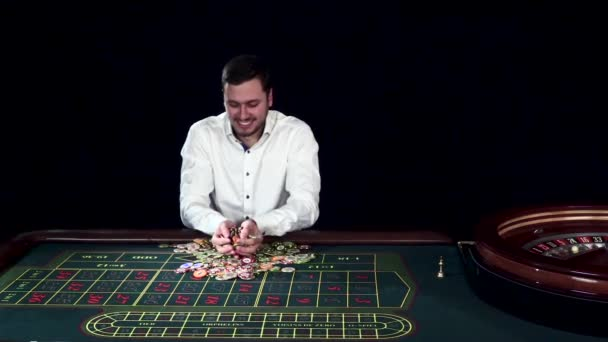 Man tossing gambling chips in a casino. Black. Slow motion