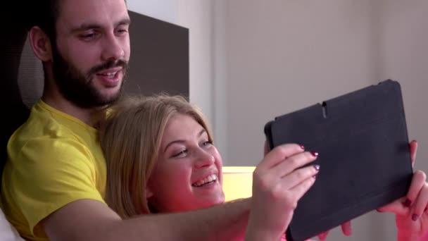 Představa mladého kluka a jeho přítelkyně, jak čtou něco na tabletu, se zamaskují