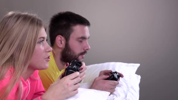 Young couple in bright pajamas, pillow fight, slowmotion