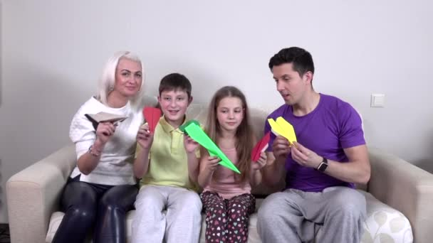 Family launches colorful paper airplanes in the room, slowmotion