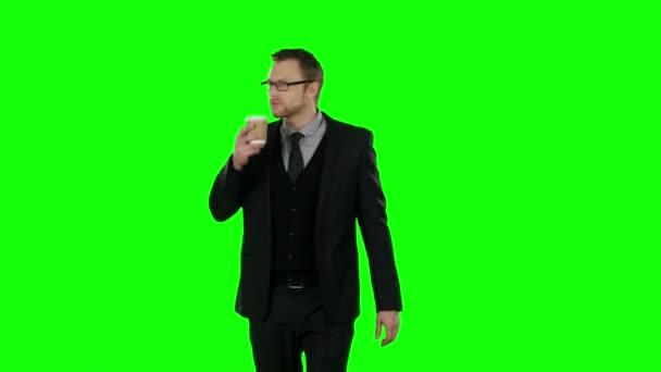 Obchodní muž, chůzi a pití kávy. Zelená obrazovka