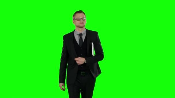 Obchodní muž chůzi a používání notebooku. Zelená obrazovka