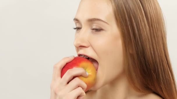 Blonde girl with braces eating apple. White. Closeup