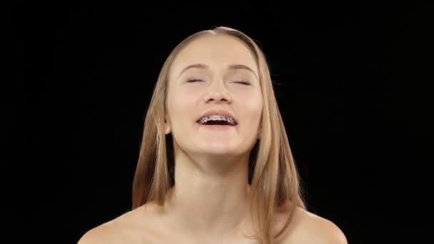 Frau lacht und zeigt ihr Lächeln mit Hosenträgern. Schwarz