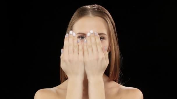 Modell deckt ihr Gesicht mit ihren Händen, und zeigt dann sein Lächeln mit Hosenträgern. Schwarz
