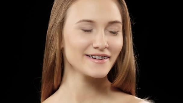Schönes Mädchen mit Zahnspange auf seine Zähne weiß posiert für die Kamera. Schwarz