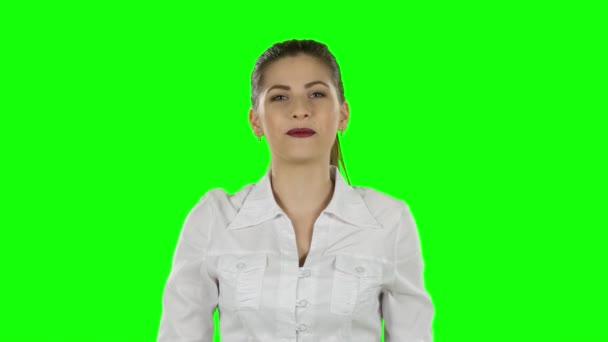 Mladé ženy představují něco rukou. Zelená obrazovka