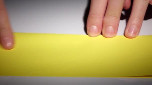 Dívka je papír origami ze žlutého papíru. Closeup