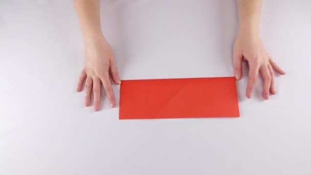 Girl making origami. Red envelope. Time lapse