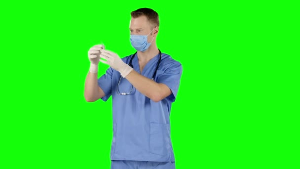 Male doctor preparing a syringe for injection. Green screen