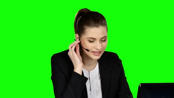 Businesswoman in headphones speaking. Green screen