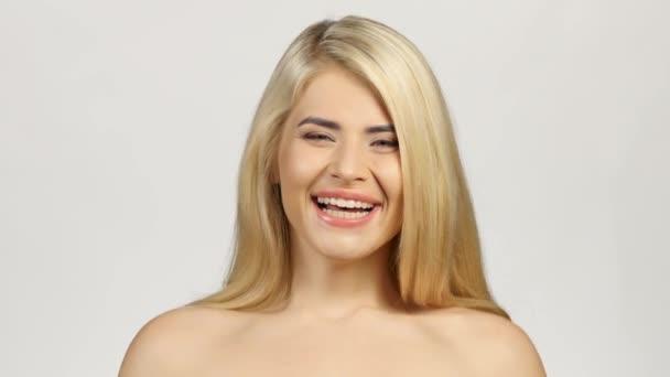 Blondýnka usmívající se čelem vzad. Bílé