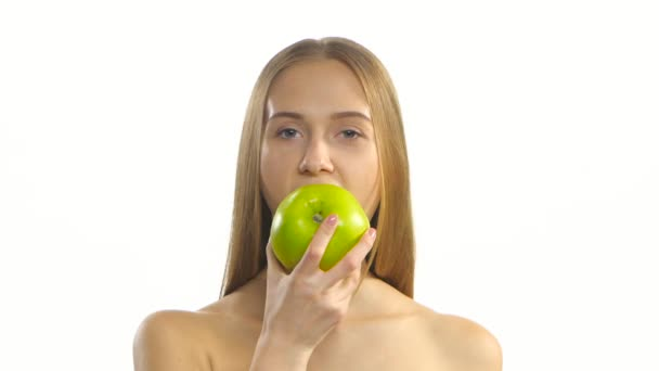 Young blonde model eating a big green apple and smile. White. Closeup