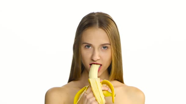 Girl with braces and red lips eating a banana and looking at the camera. White. Closeup