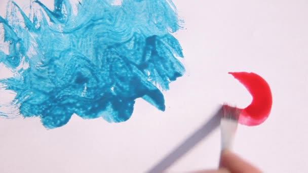 Zeichnung mit Pinsel mit blauer, rosa und orangefarbener Farbe auf einem Papier.