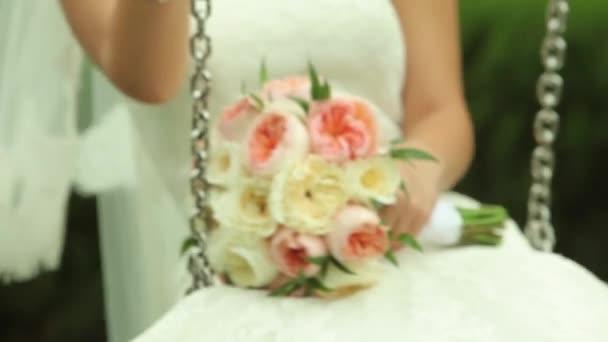 Sposa doscillazione in altalena e che tiene il suo bouquet di fiori