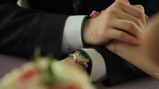 Nevěsta a ženich drží za ruce, dynamická změna zaměření na kytice květiny