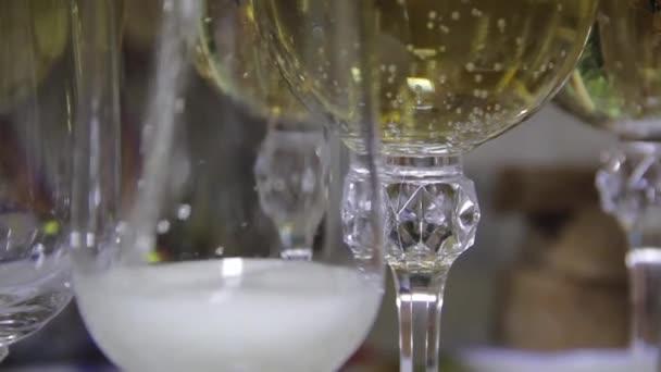 Champagner in Gläser auf der Festtafel gießen