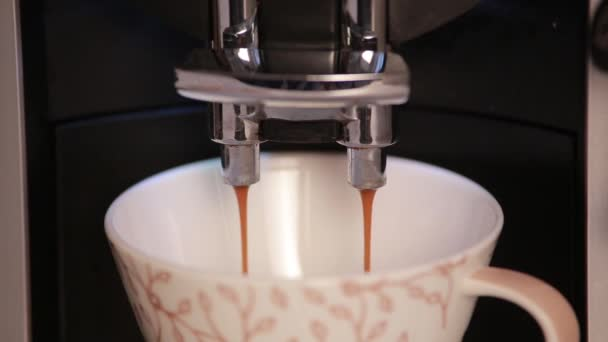 Coffee maker fills ceramic cup of coffee.