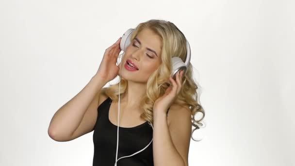 Krásná kudrnatá blondýnka na sluchátkách poslouchá hudbu. Bílé. Zpomaleně