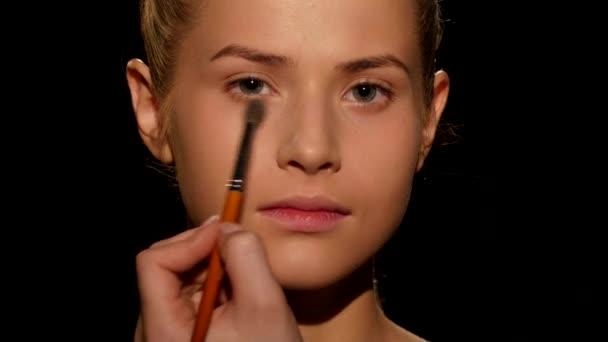Professional make-up artist. Make-up artist doing make-up. Black. Closeup
