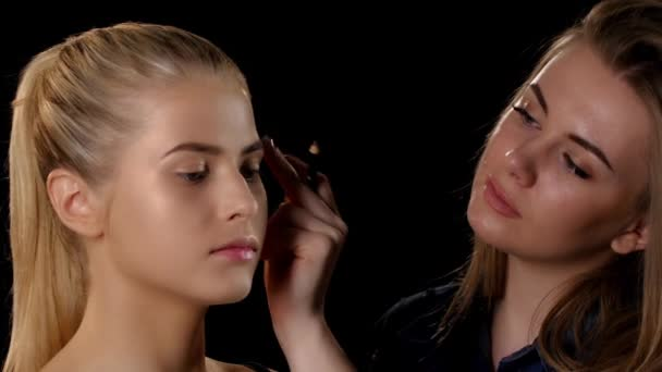 Makeup artist applying makeup to young blonde girl. Black. Closeup
