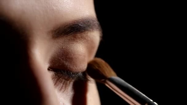 Artist applying eyeshadows. Black. Makeup. Closeup