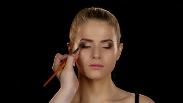 Makeup artist makes models eye makeup. Black. Closeup
