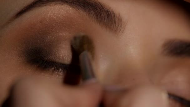 Makeup artist working on a young girl beauty. Eyeshadow. Closeup