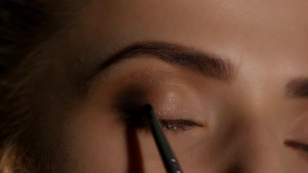 Makeup artist makes a girl beautiful makeup before an important event. Closeup