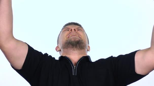 glücklicher Mann, der mit erhobenen Armen feiert. weiß. Zeitlupe