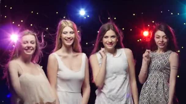 Čtyři dívky tančí spolu a foukání polibky v disco