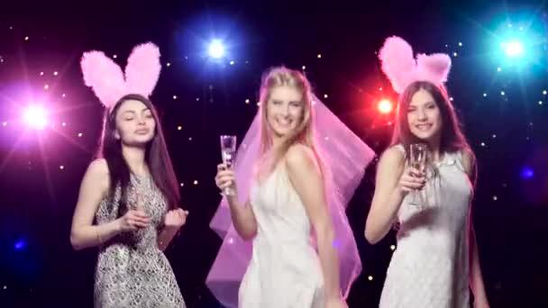 Glückliche Braut mit Freundinnen tanzen trinken Champagner auf Bachelorette party