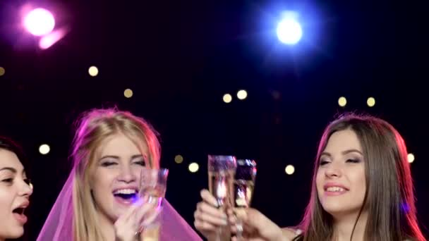Girlfriends raise their glasses and drinking champagne at bachelorette party