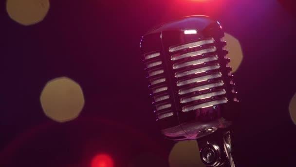 Vintage mikrofon a sötét elmosódott háttér ellen, fényes villogó fények