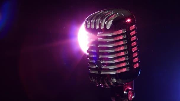 Klasszikus mikrofon lassan forog a háttérlámpa stroboszkóppal sötét