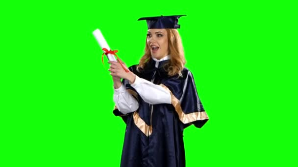 Girl with graduation gown and diploma. Green screen