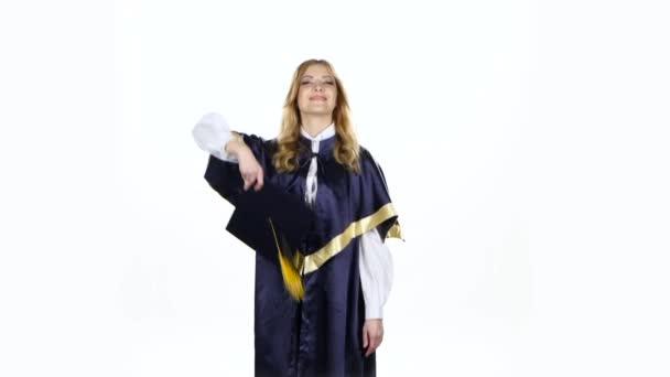 Absolventi hází do vzduchu čepici. Bílé