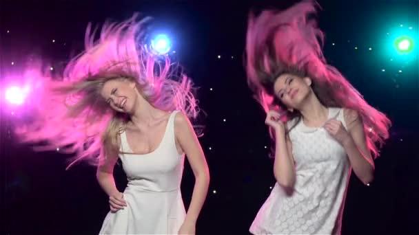 Děvčata tančí s podobnými posunky. Zpomaleně