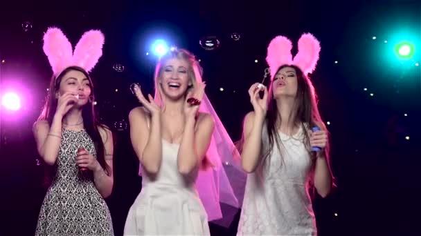 Happy girls at bachelorette party blowing soap bubbles. Slow motion