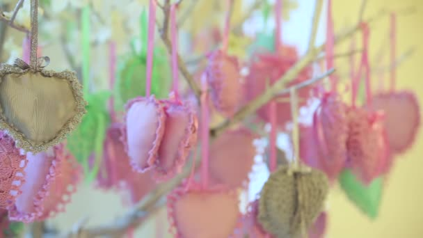 Decorations of hearts are hanging from tree. Dynamic change of focus. Close up
