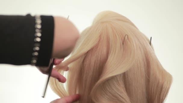 Účes na vlasy. Kadeře v výkon holiče. Bílá. Zblízka